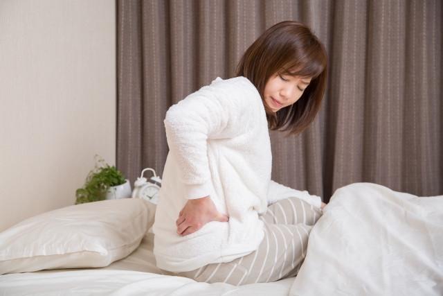 腰痛で起きるのが辛いと悩む女性